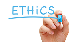 Hand writes the word ethics